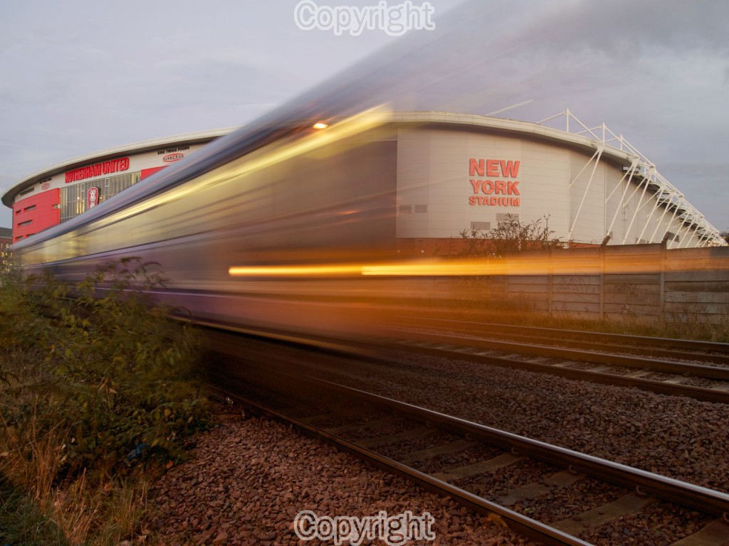 I Photographed the train passing the new york stadium. The train was traveling relatively slowly I used a longer exposure to give the sense of speed.